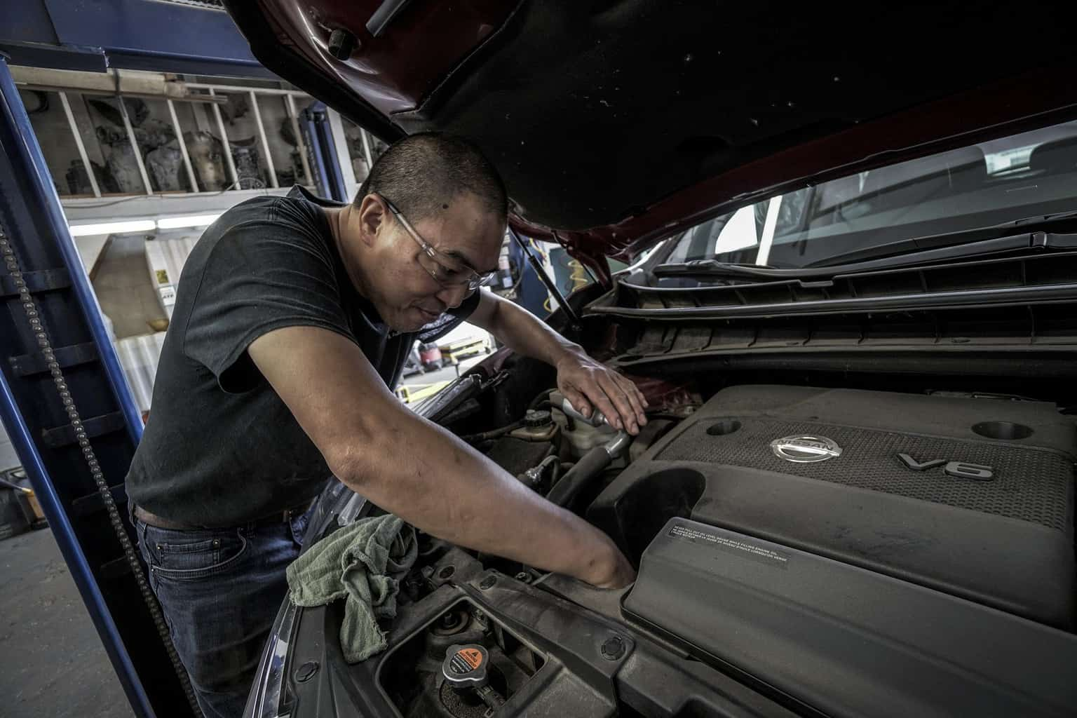 A man changing the oil of a car