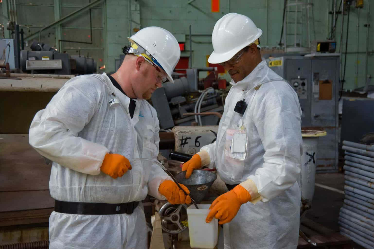 Two men with protective equipment and gloves holding a metal
