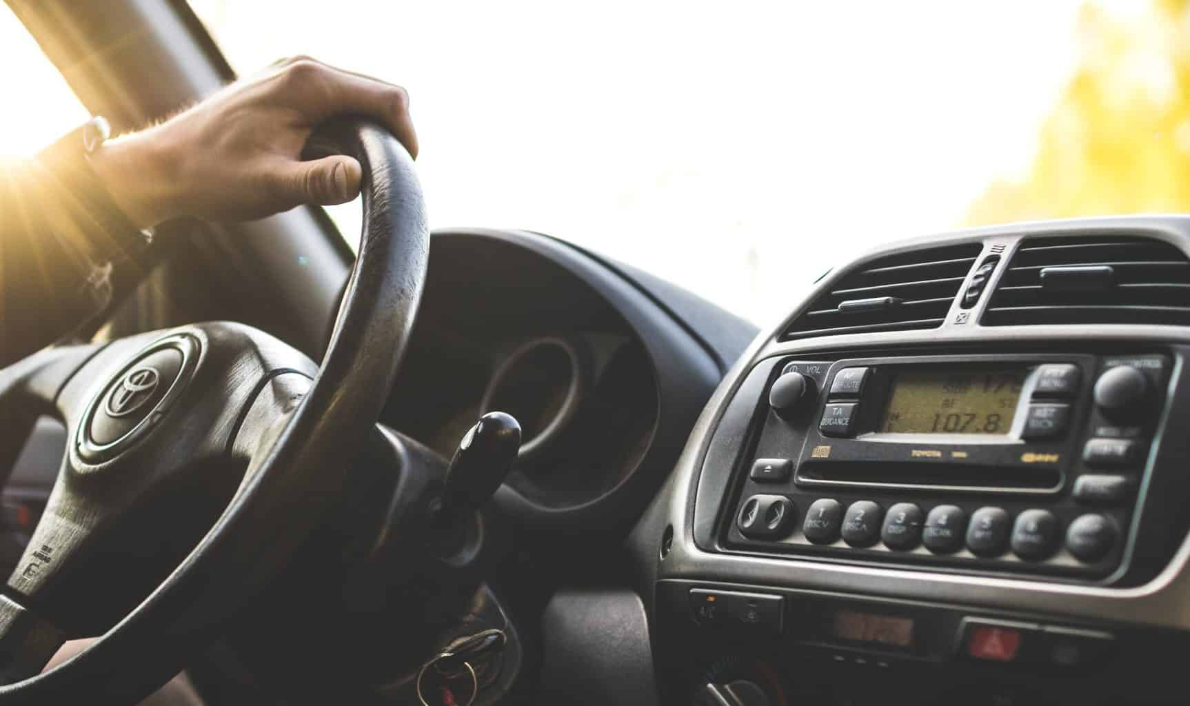 A shot inside a car with a steering wheel and a sound system