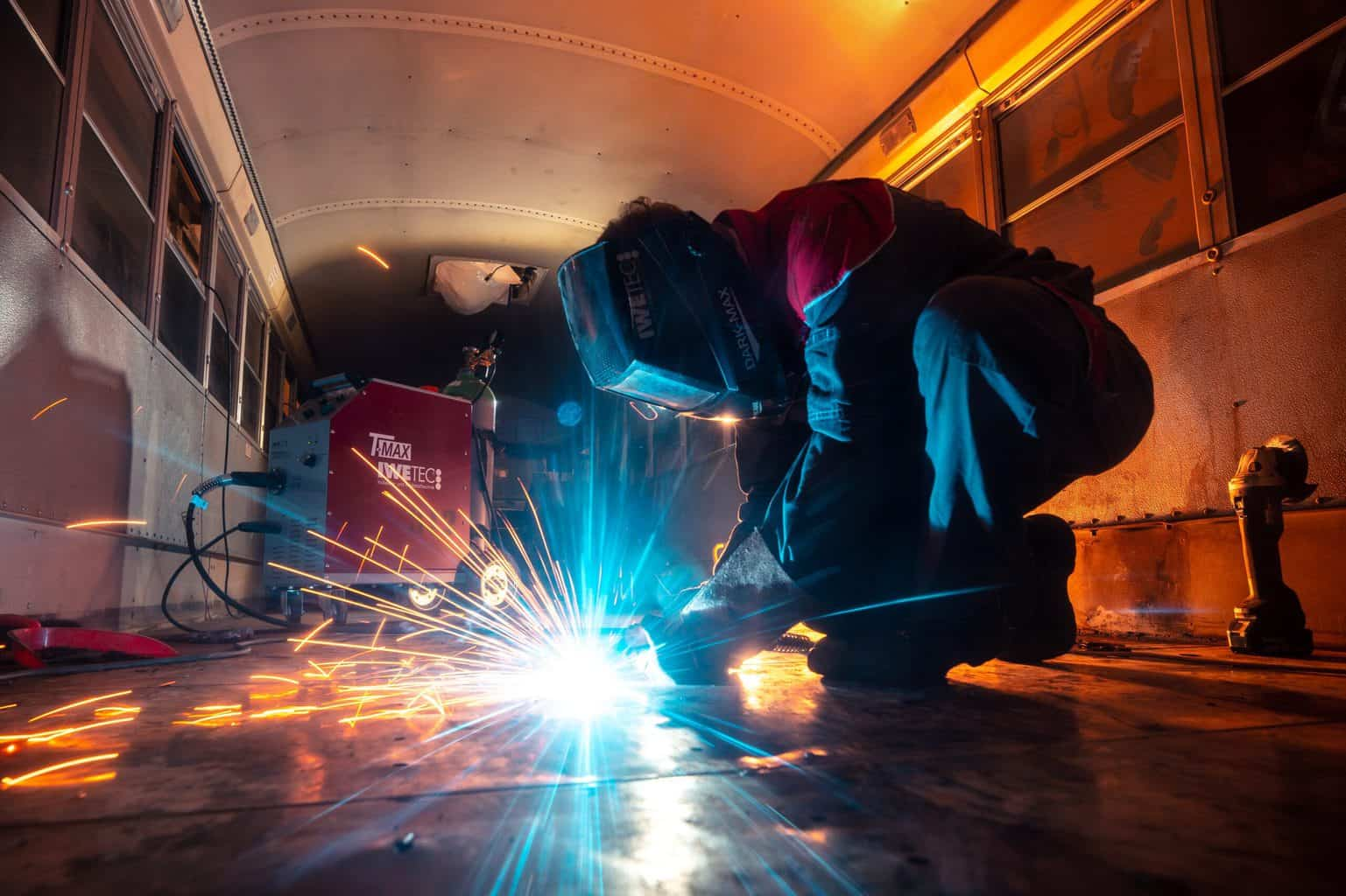 Person handling steel with sparks and protective equipment