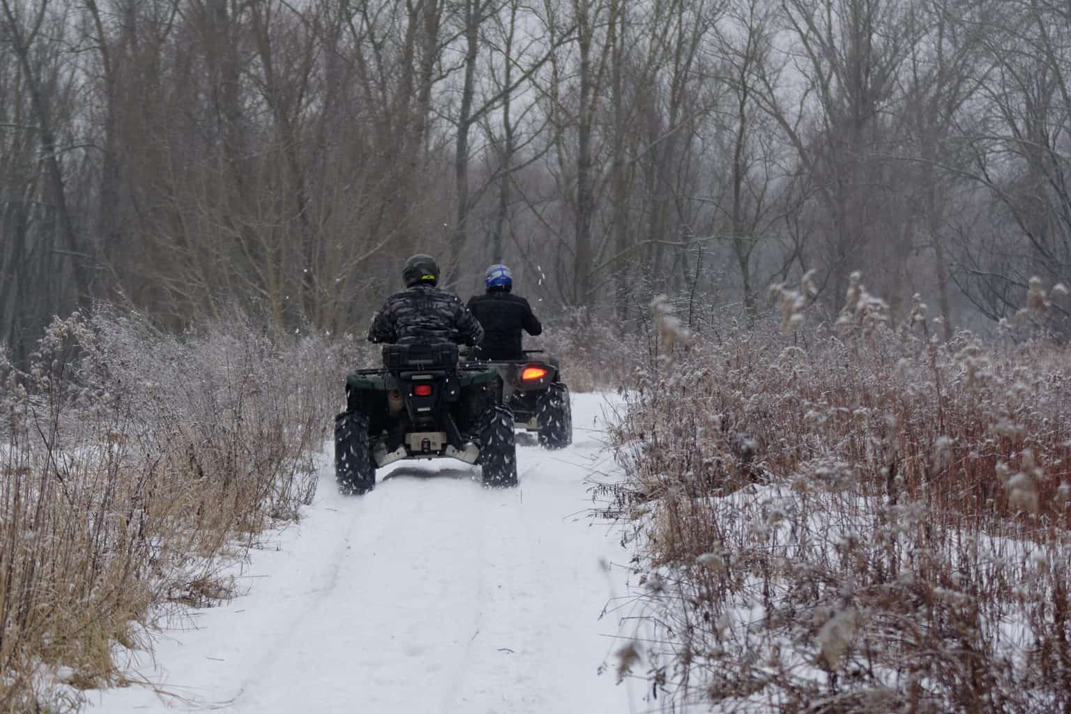 Two persons riding two ATVs in snow