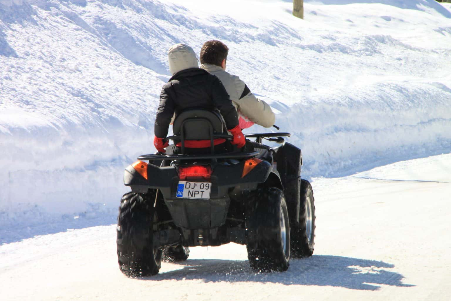 Two people riding an ATV in snow