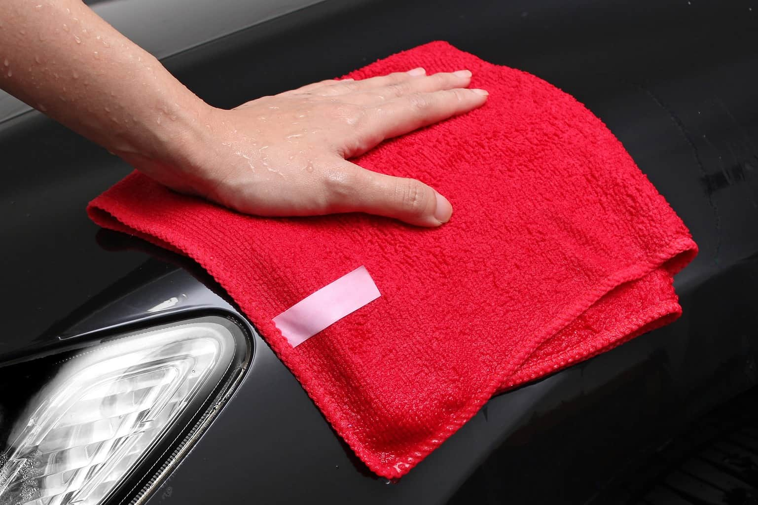 Wiping the headlights of a car with a red towel
