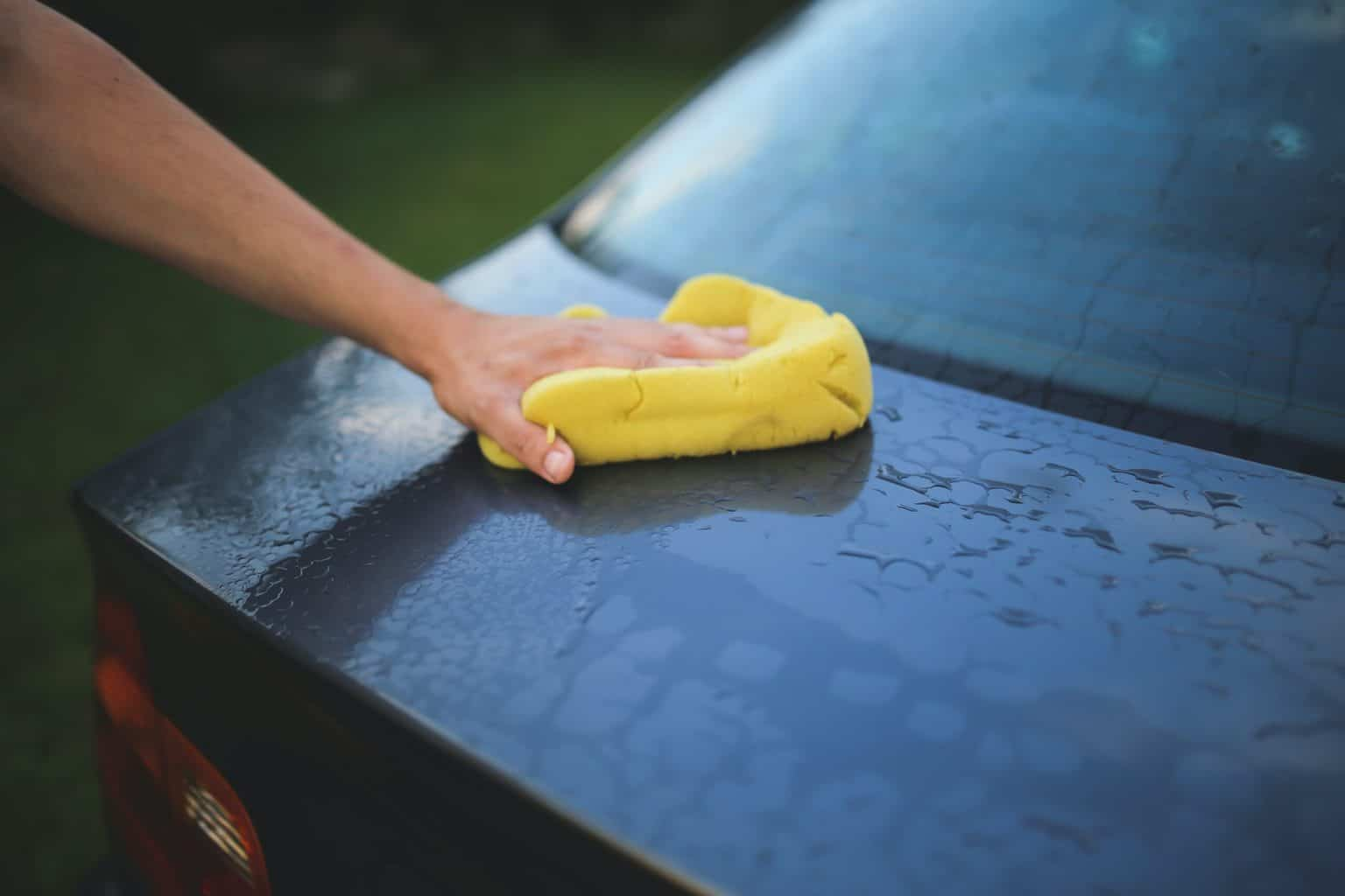 Wiping the back of the car witha yellow towel