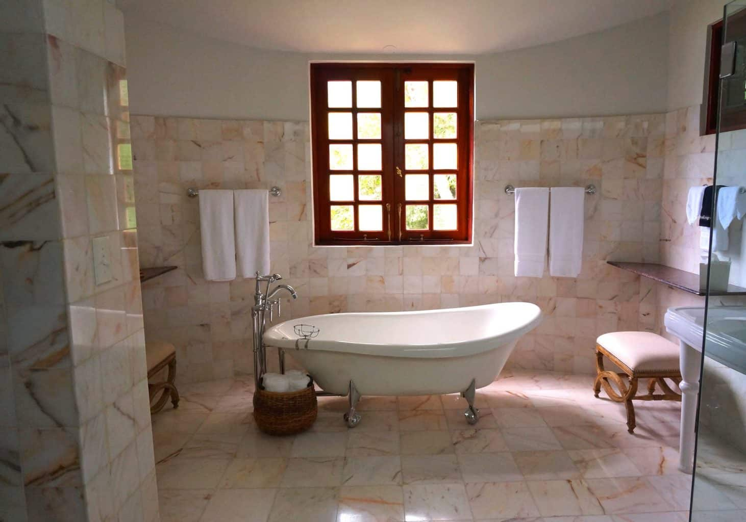 A bathroom with tiled walls and a bathtub at the center