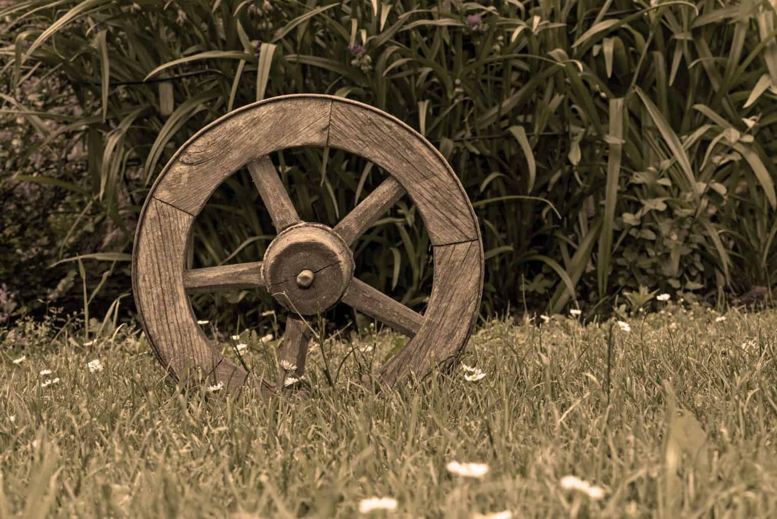 A wooden wheel on top of green grass