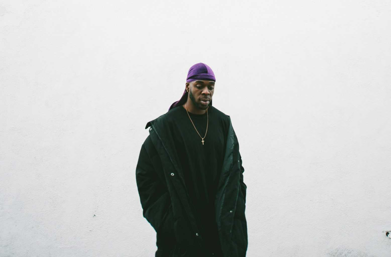 A man wearing black clothes with a purple durag