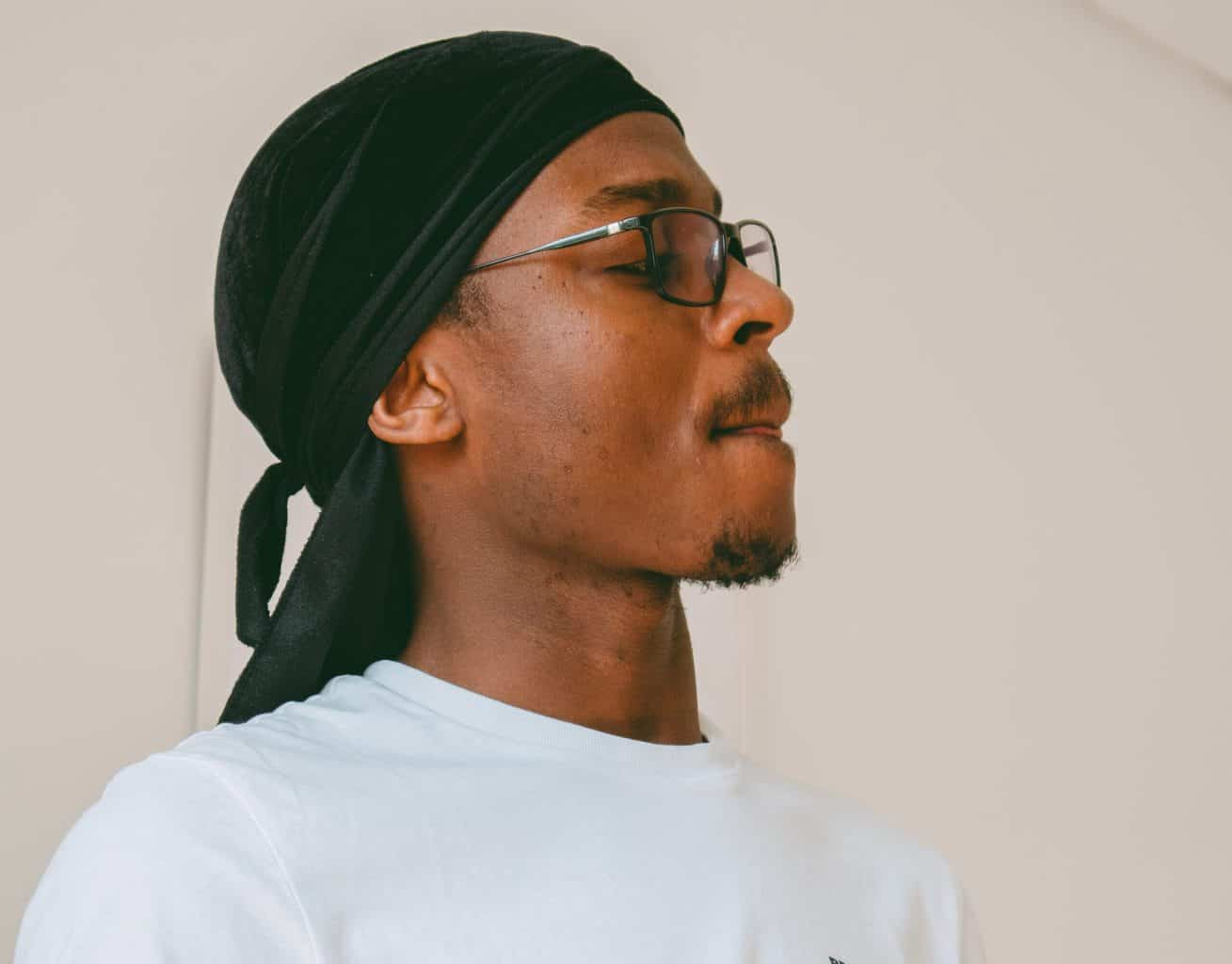 A man with glasses wearing a black durag