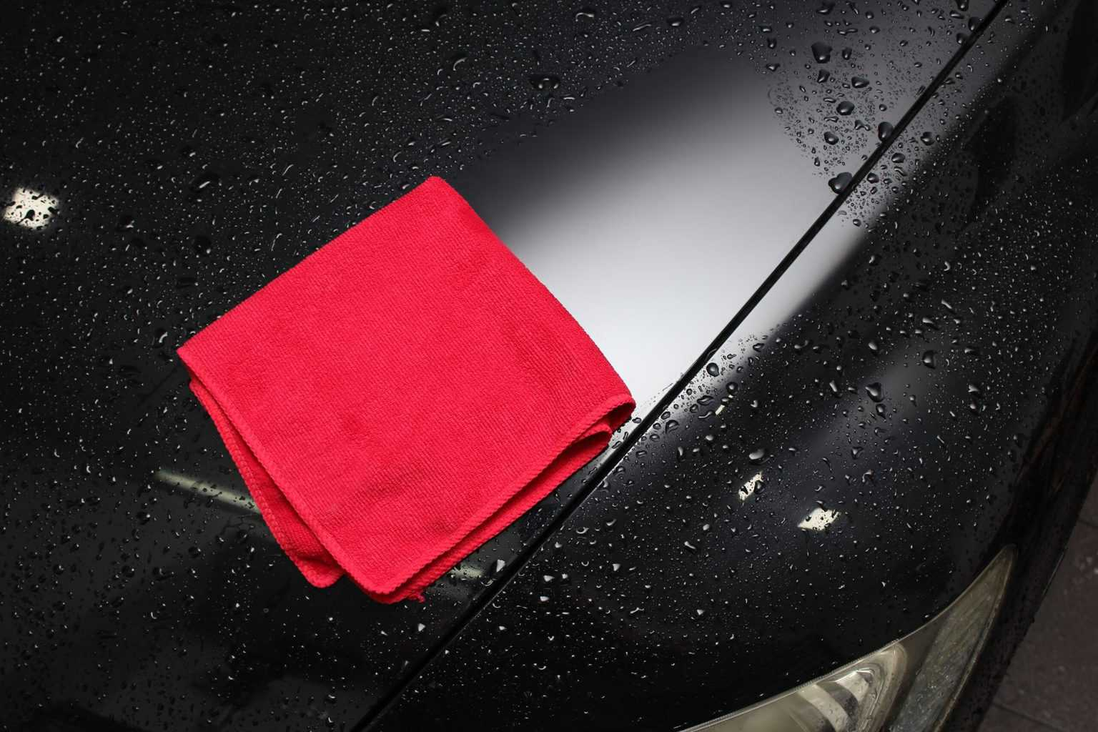A shiny car wiped with a red cloth