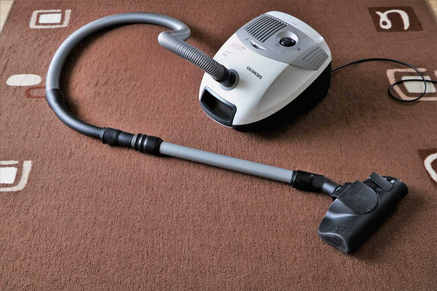 A white vacuum cleaner on a brown carpet
