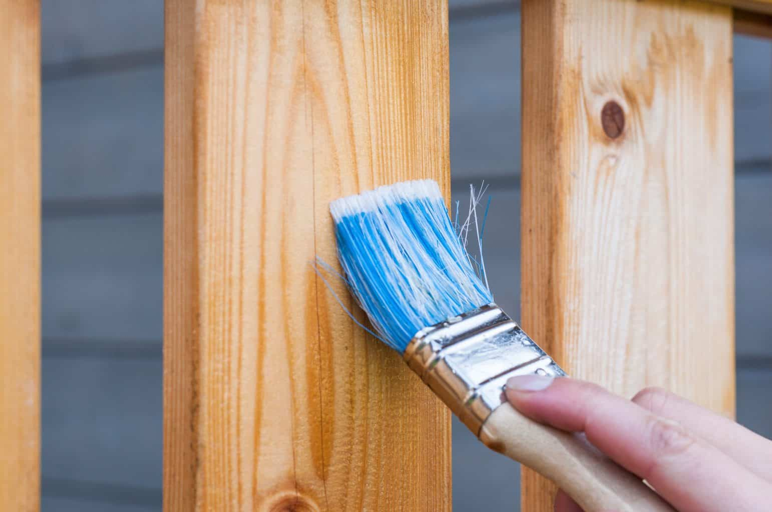 A blue paint brush shining the wood
