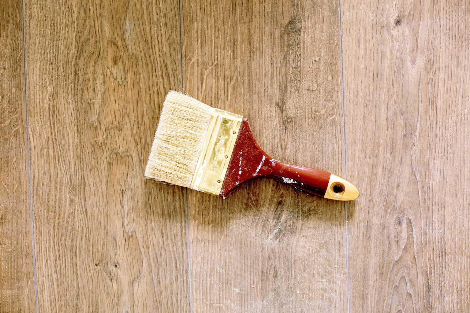 A paint brush on top of a wood