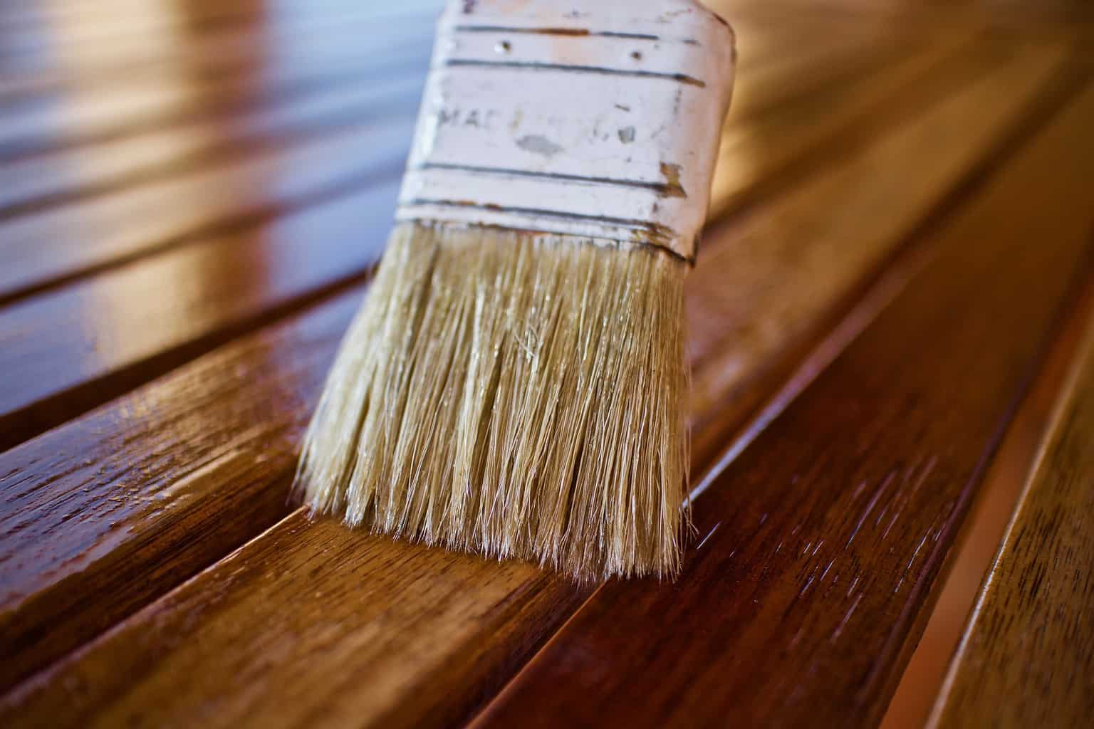 A close up shot of a paint brush shining the wood
