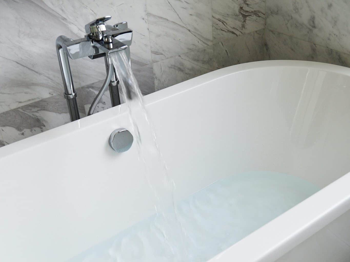A bathtub with running water in faucet