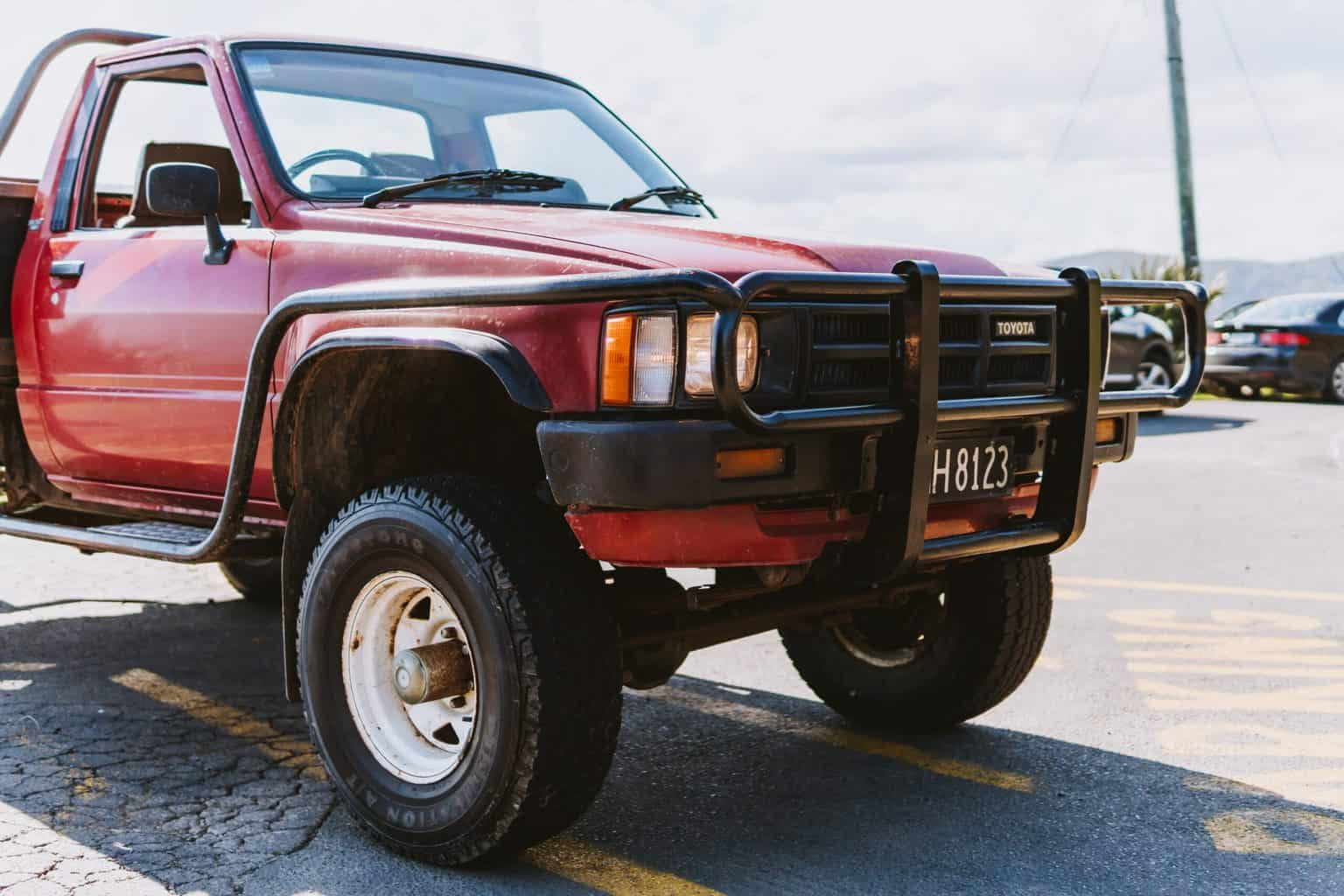 A front view of a red truck with a grille guard