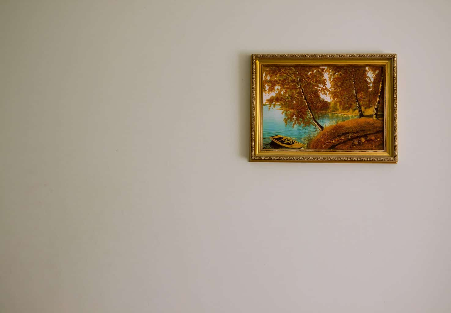 A golden poster framed and mounted on a white wall