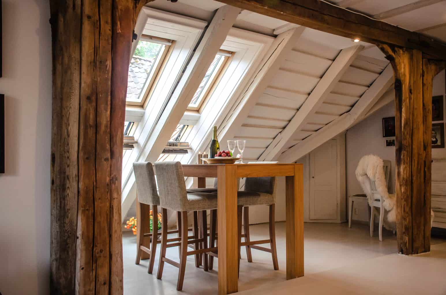 Wooden columns with a wooden dining table near the window
