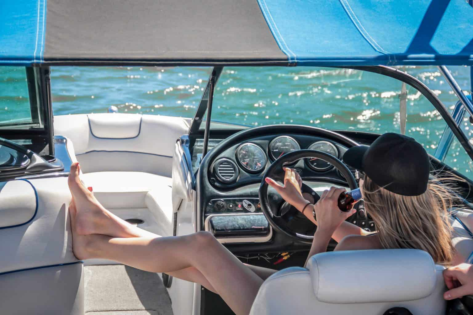 A woman sitting on a boat taking the steering wheel