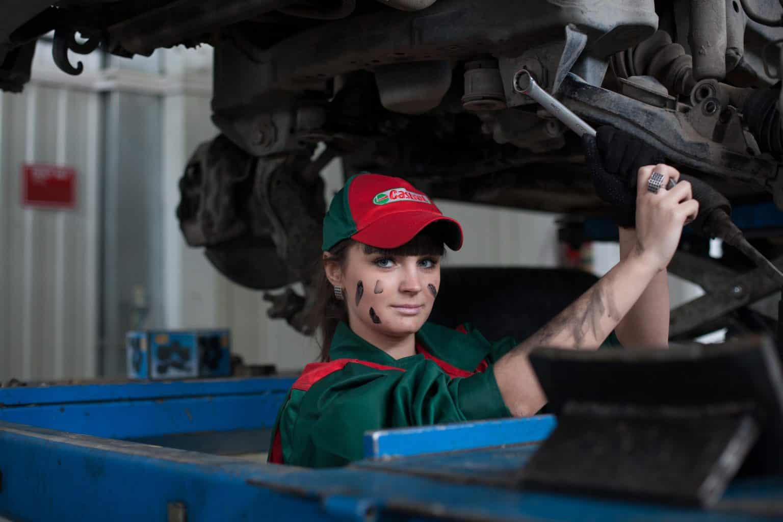 A woman fixing the engine under the vehicle