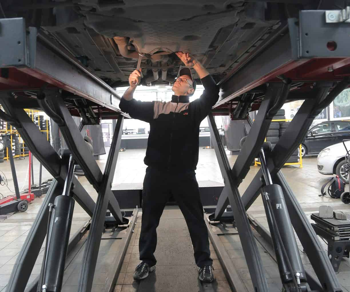 A mechanic standing under the vehicle fixing an engine