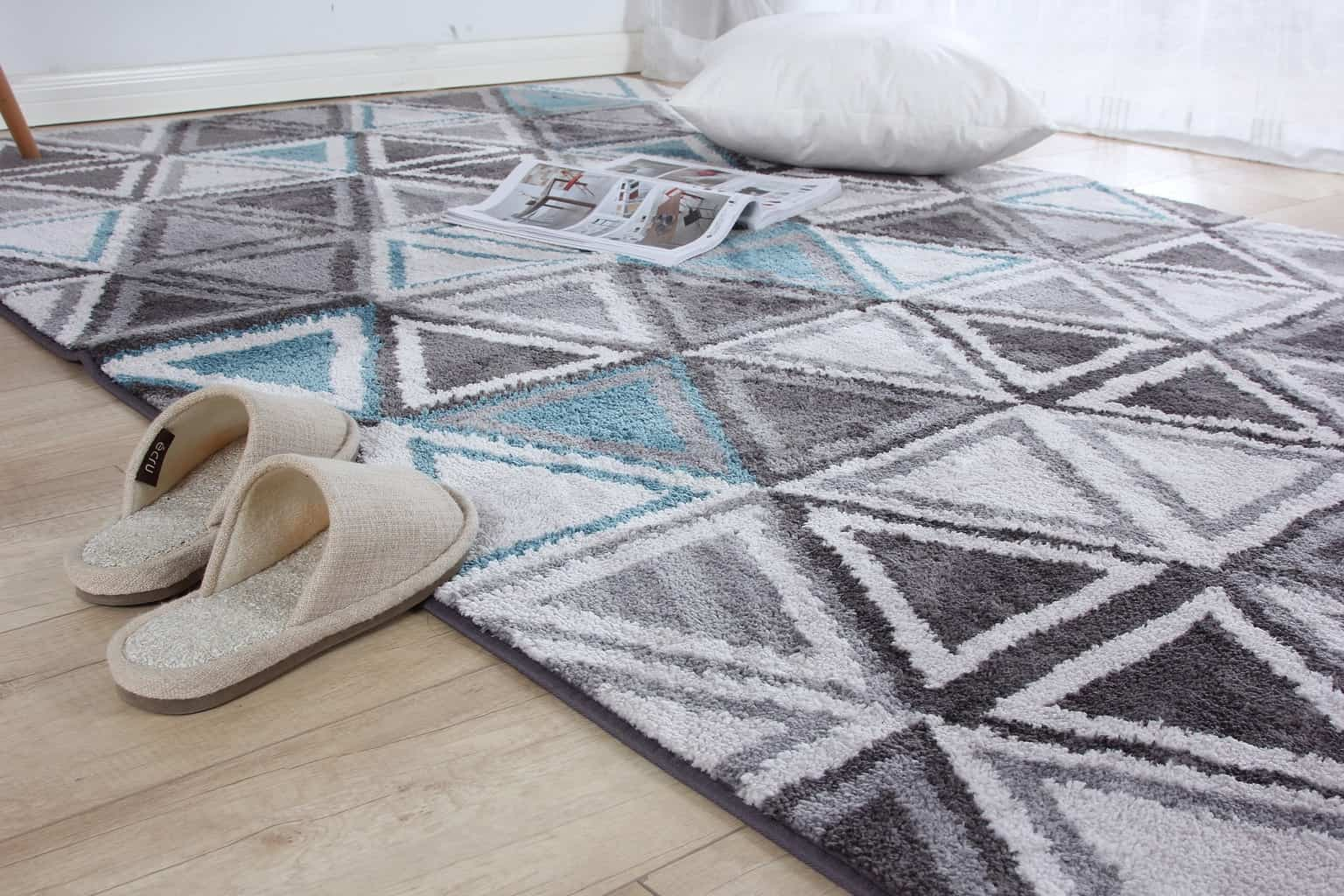 A carpet with a pillow and slippers