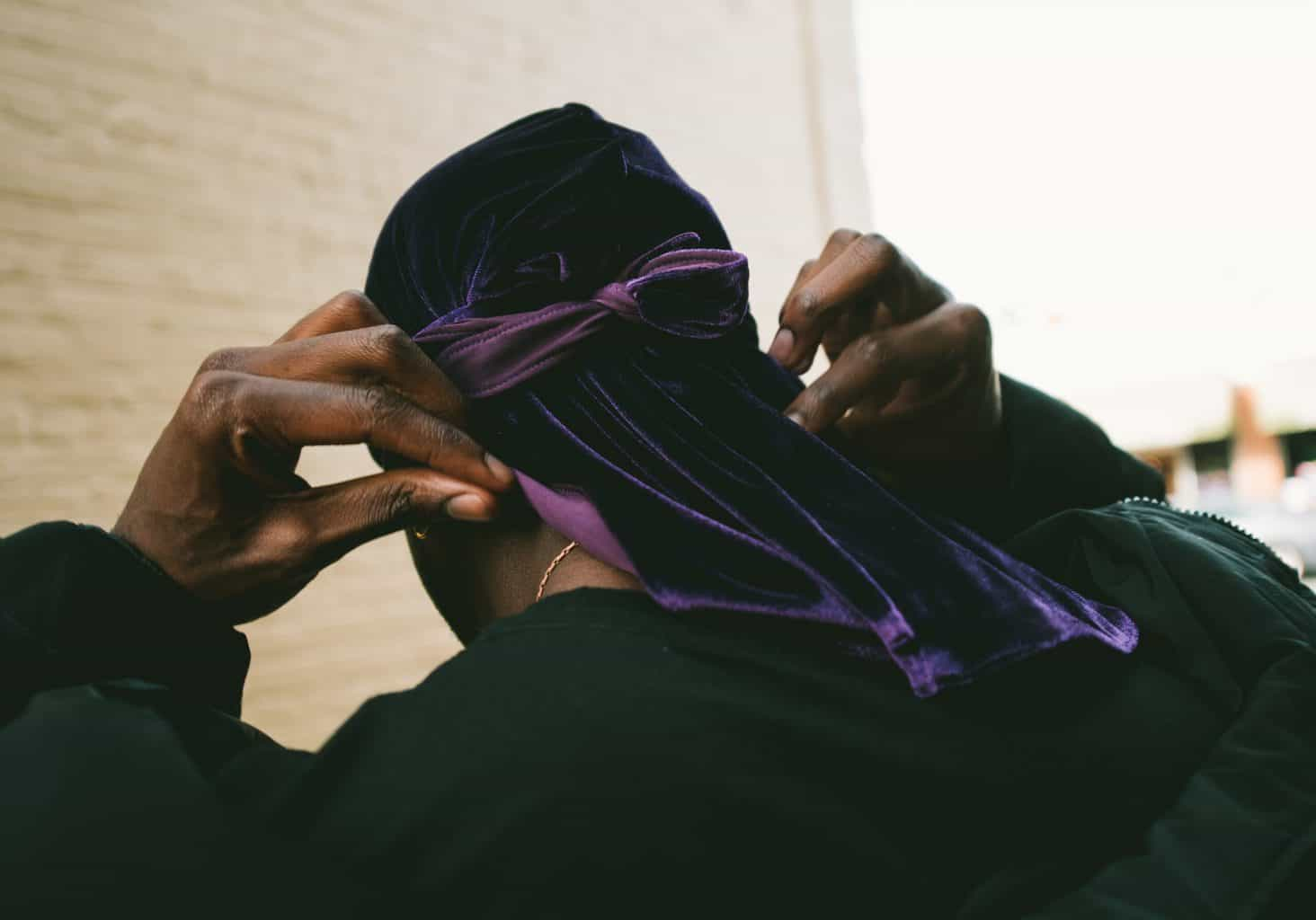 A rear view of a man holding his durag