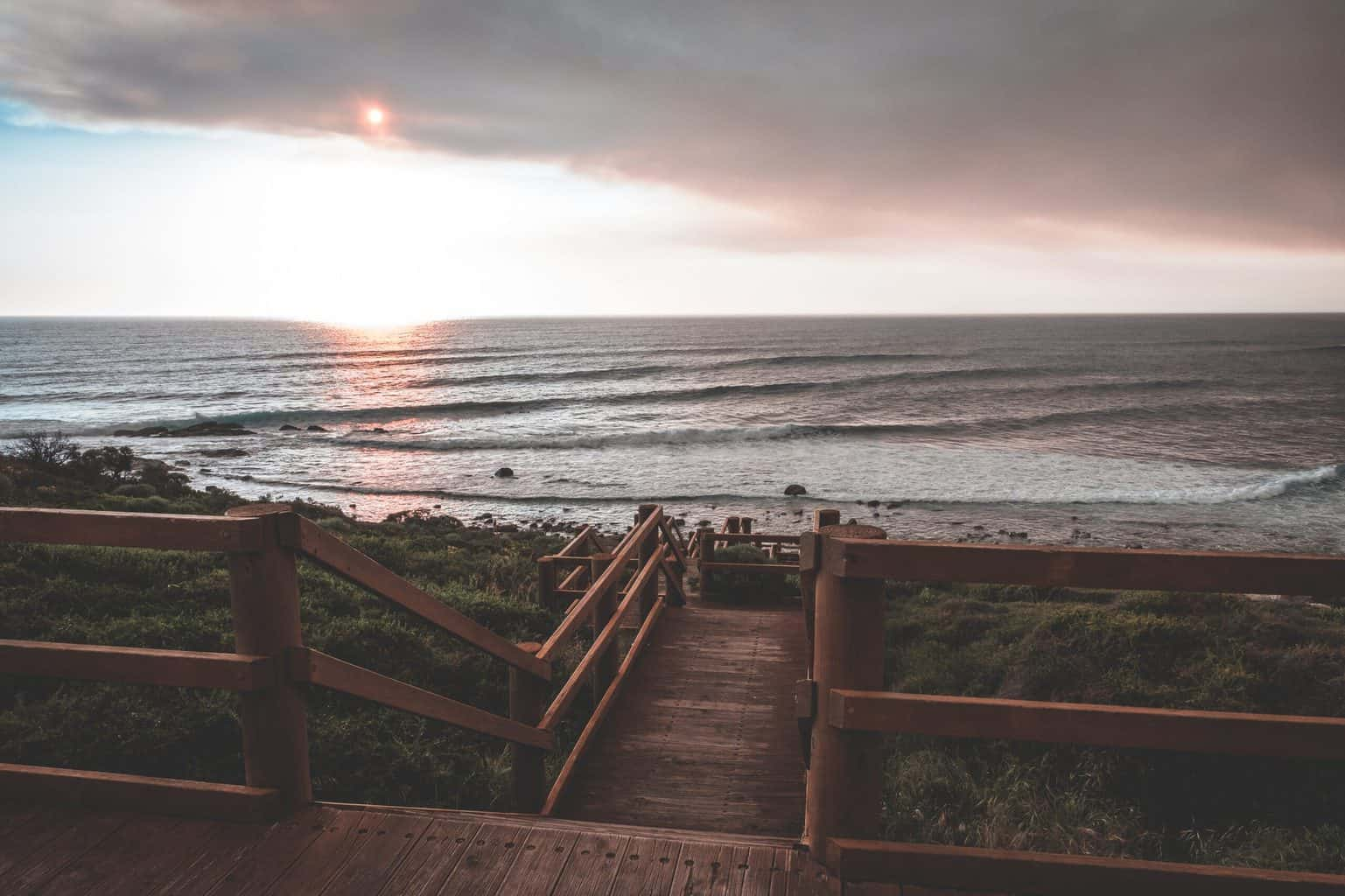 Wooden steps with sunlight on horizon and sea