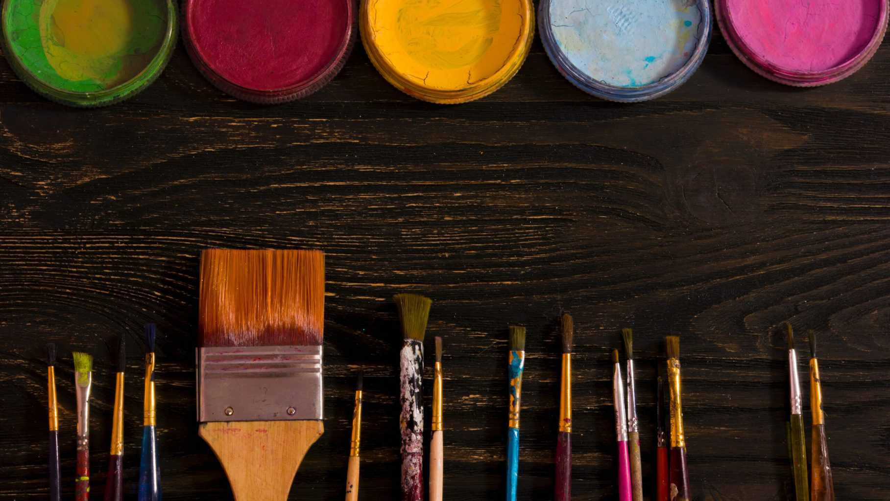 Paint brushes and paint on top of a table