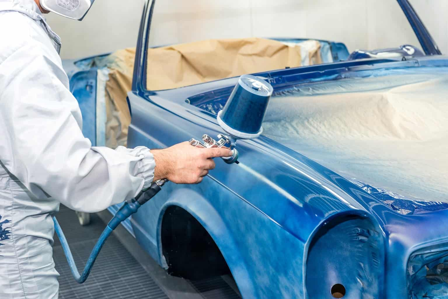 Spraying a blue color to a car with a powder coating gun
