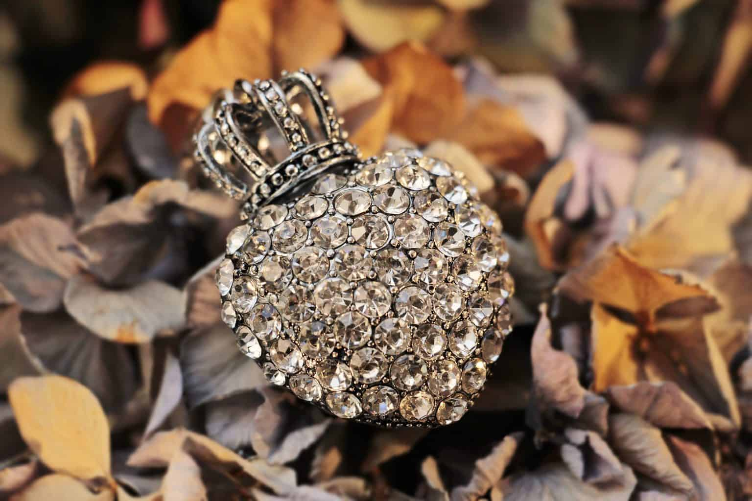 A heart shaped jewelry with rhinestones and a small crown