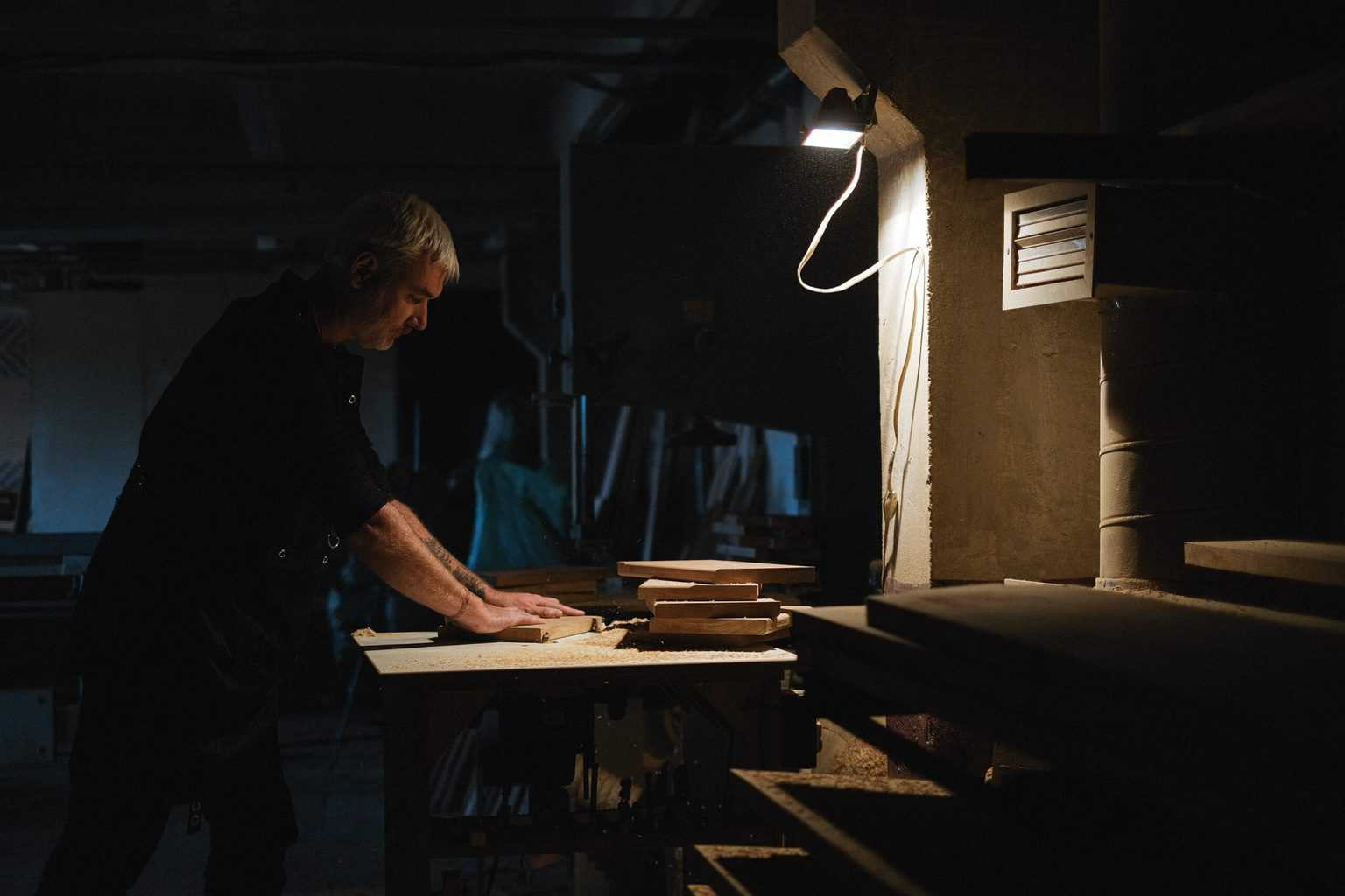 A man handling wood with small light
