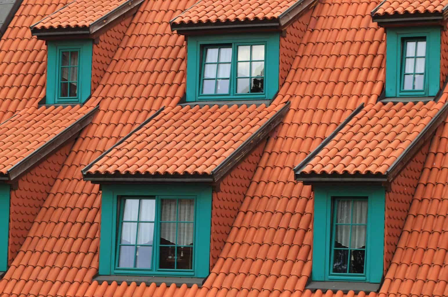A close up shot of an orange toned roof with windows