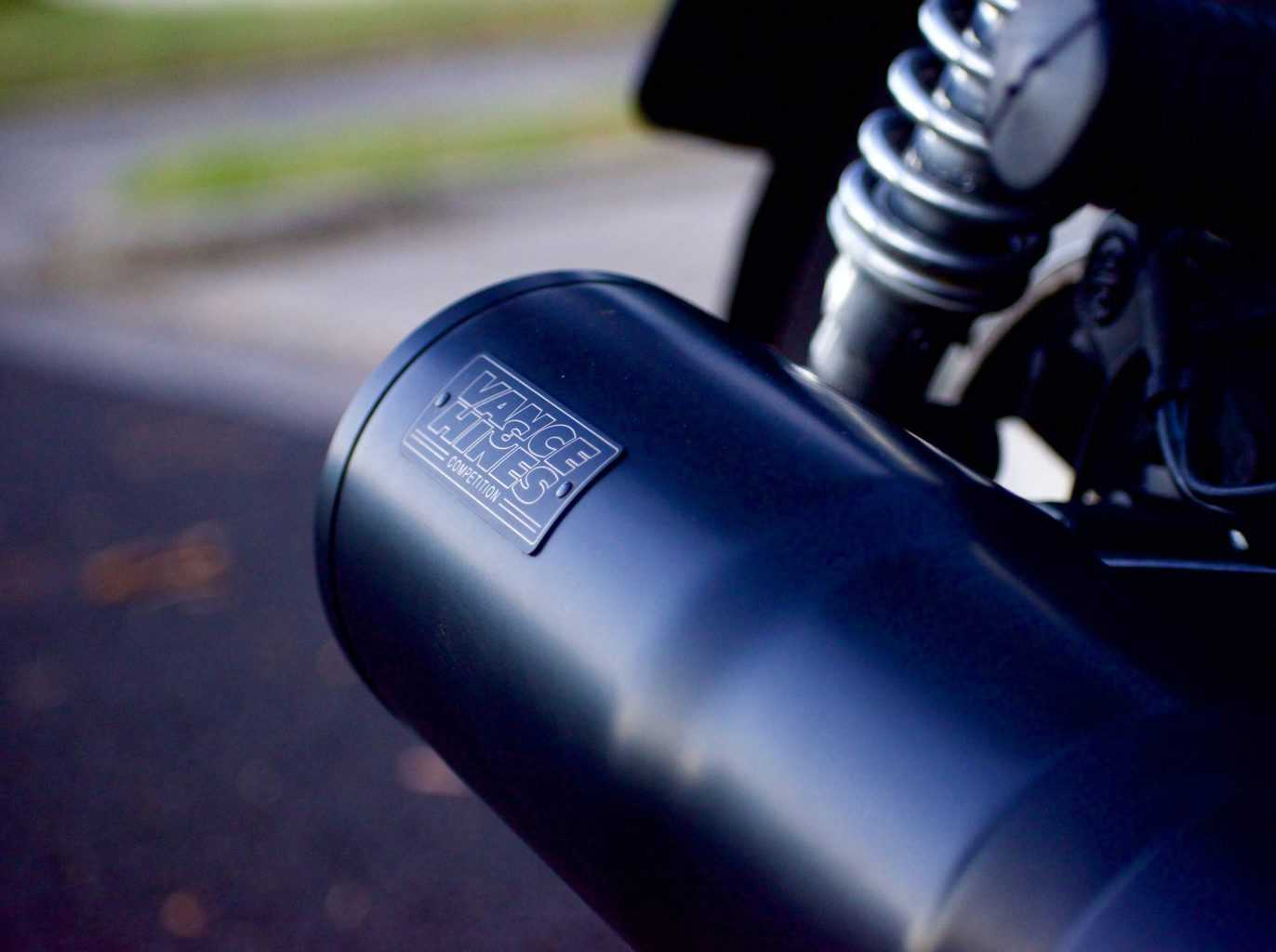 A close up shot of a black exhaust attached to the bike