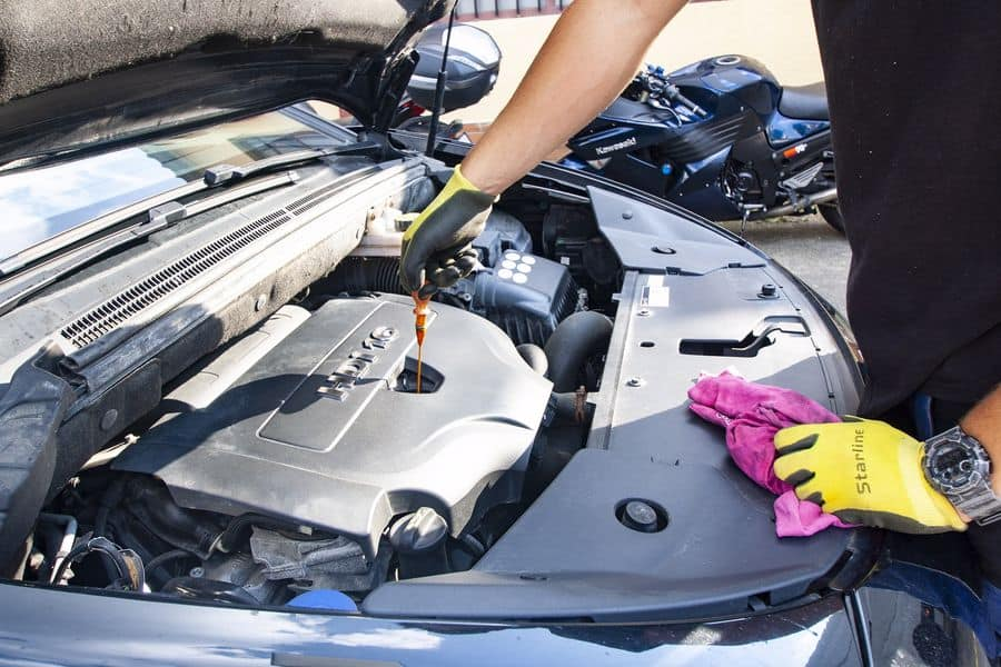 Person changing a car engine oil