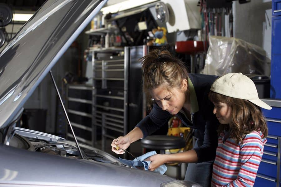 Mother and daughter working on car engine