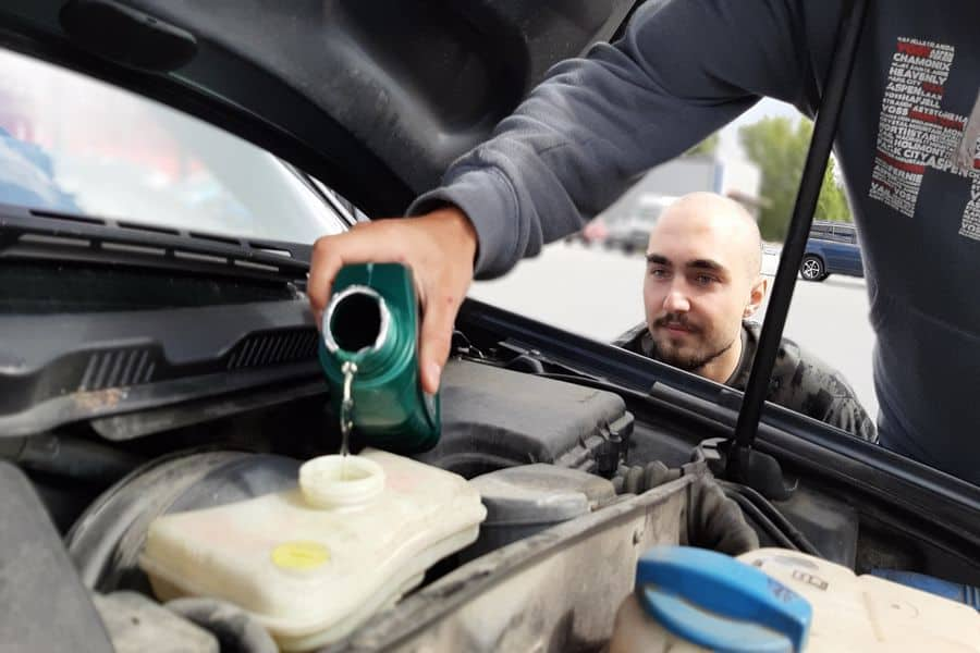Man observing his friend as he pours oil on a car engine