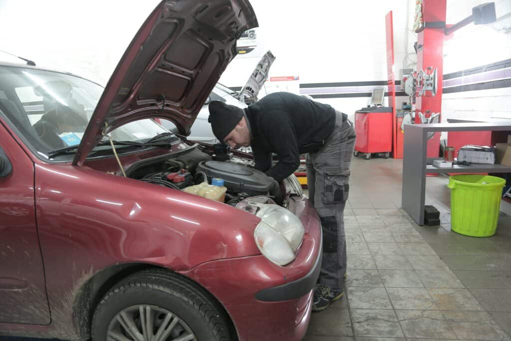 A person inspecting an engine of a red car