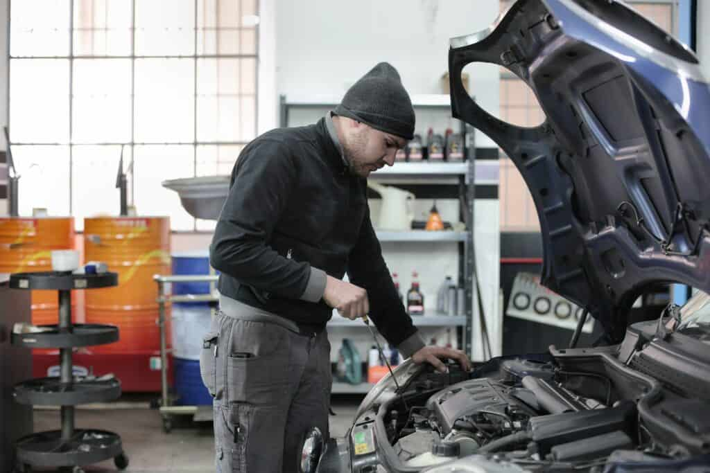 A man inspecting the engine of a car