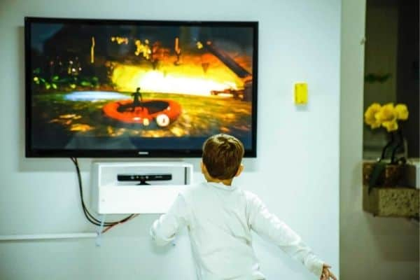 A child watching a TV mounted on a drywall