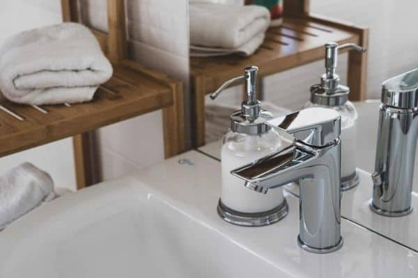 A porcelain sink with a chrome faucet and a soap dispenser