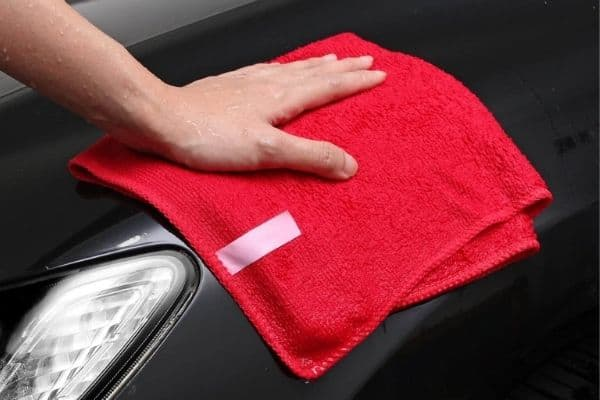 Hand wiping a car with a red microfiber cloth