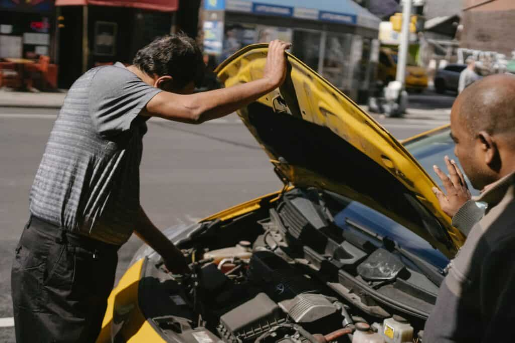 Two people checking a car engine of a yellow car in a sunny day