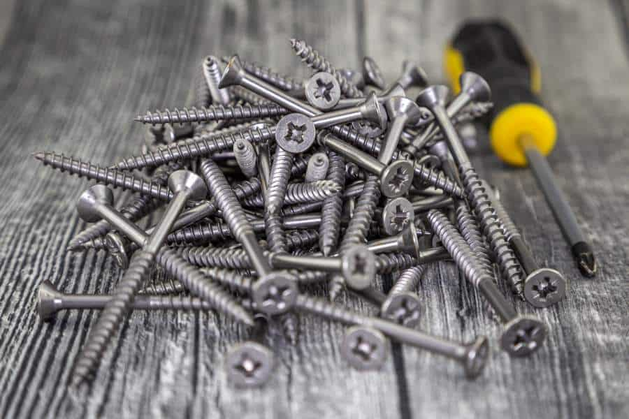 A pile of Philips screws and a screwdriver