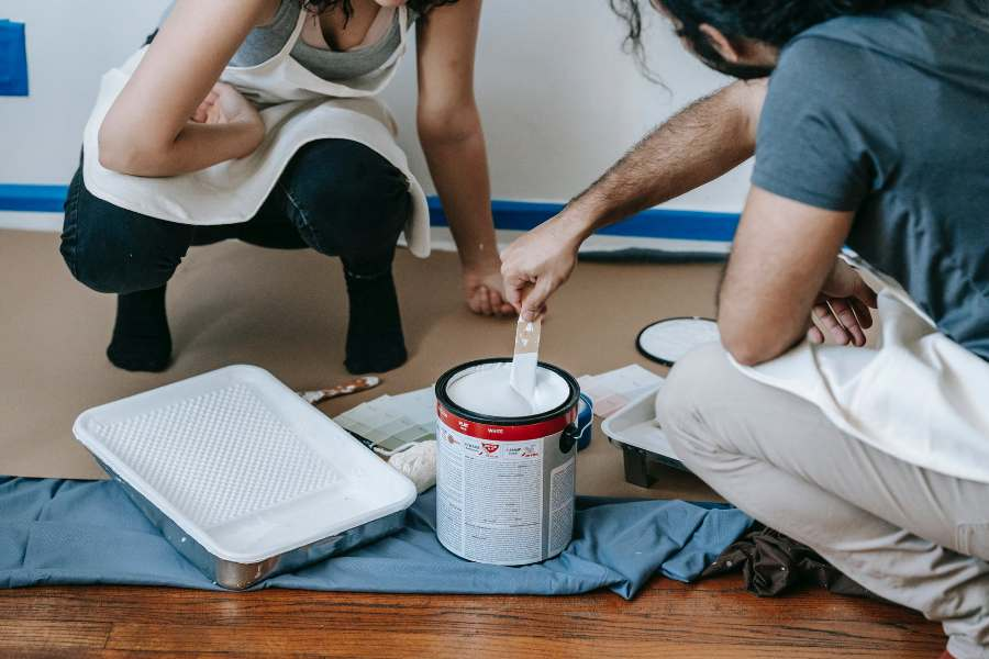 Couple mixing in a primer before painting their wall