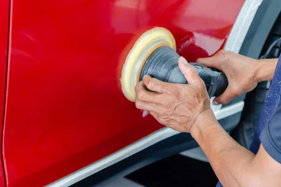 Person using a buffer to remove car scratch