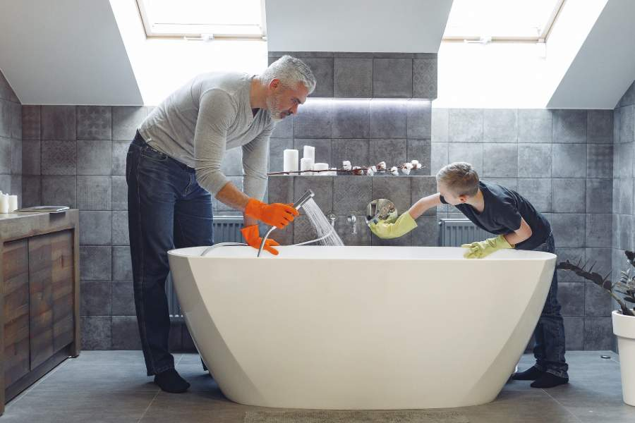 Father and son cleaning a bathtub