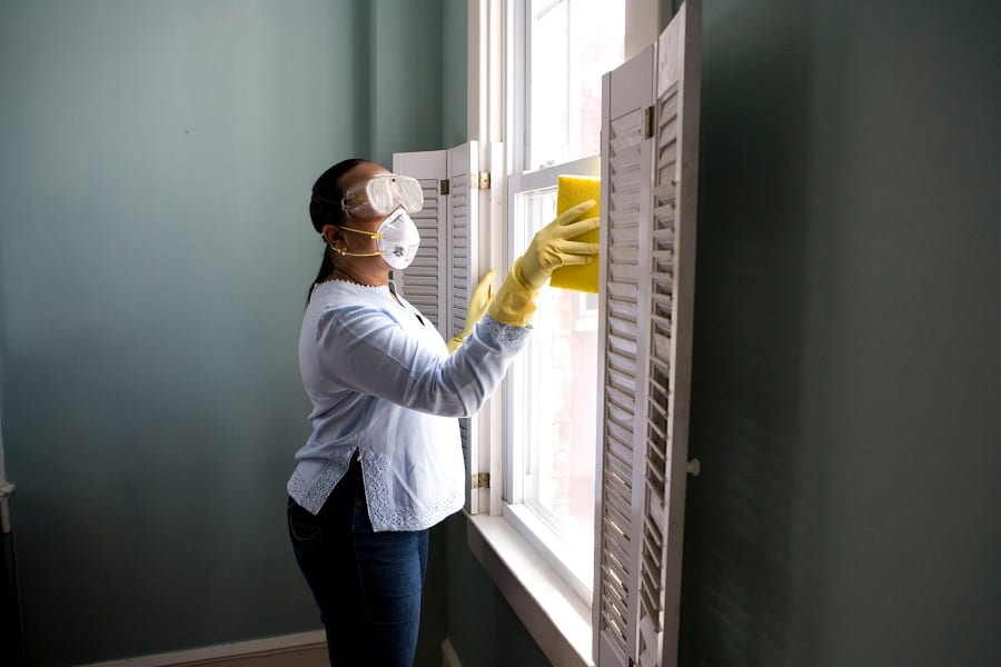 Woman cleaning a window with a damp sponge