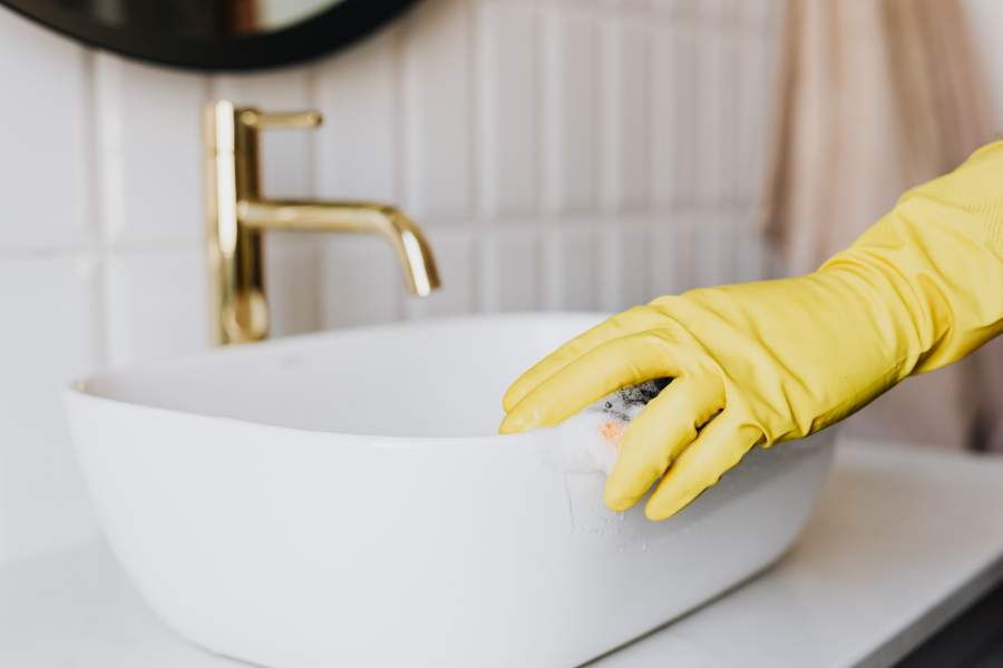 Person wearing a yellow glove cleaning a porcelain sink with a sponge