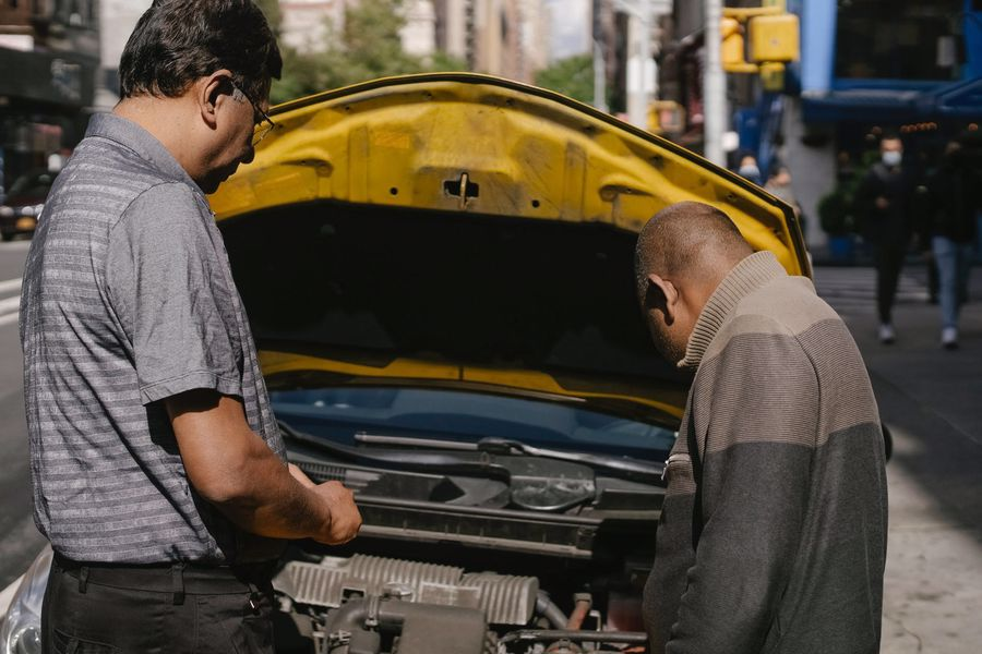 Two men checking the car's engine