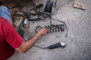 Amateur car mechanic is lowering a car with springs